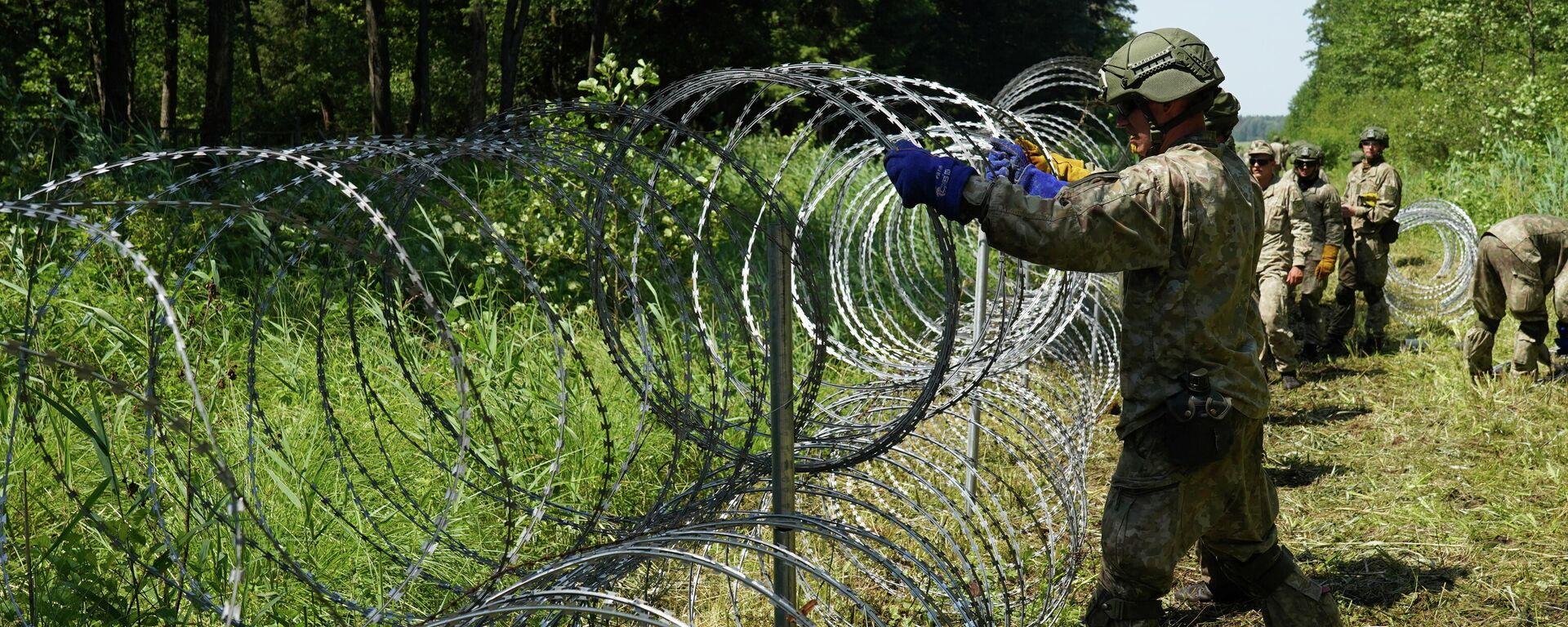 Солдаты литовской армии устанавливают забор из колючей проволоки на границе с Беларусью в городе Друскининкай - Sputnik Узбекистан, 1920, 14.07.2021