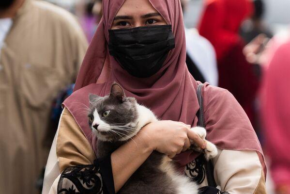 В Филиппинах мусульманка в медицинской маске несет кошку после утренней молитвы в Курбан-хайит возле Голубой мечети в городе Тагиг, метро Манила, Филиппины. - Sputnik Узбекистан