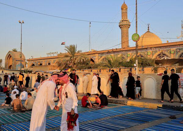 Иракские верующие обмениваются приветствиями после молитвы, совершенной в честь празднования Курбан-хайита, на улице возле мечети Абу Ханифа в районе Багдад Адхамия, Ирак. - Sputnik Узбекистан