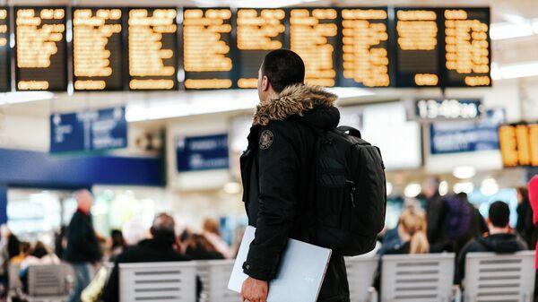 Пассажир смотрит на расписание рейсов - Sputnik Узбекистан