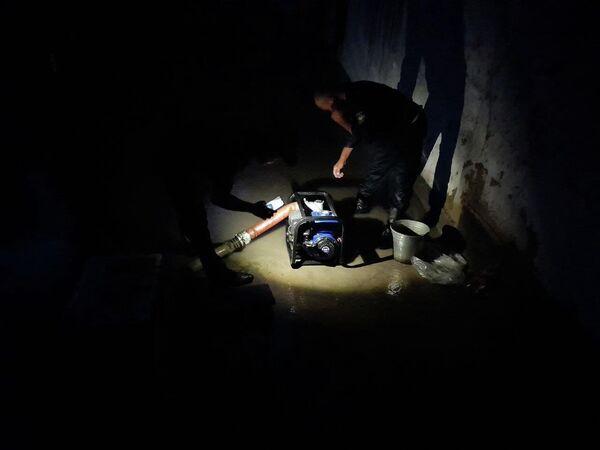 Они откачивают воду, скопившуюся в домах жителей в результате наводнений, вызванных ливнями и градом. - Sputnik Узбекистан
