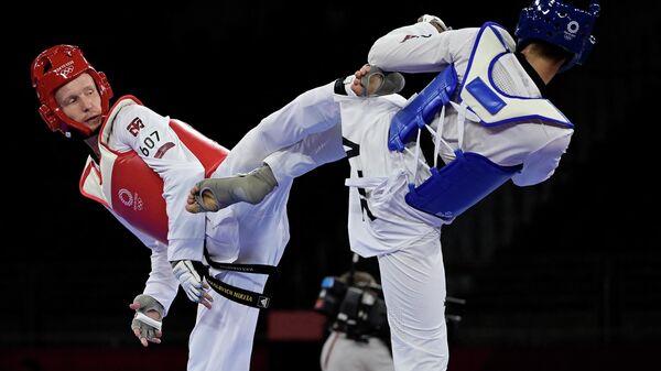Milad Beygi Xarchegani (sprava) iz Azerbaydjana i Nikita Rafalovich (sleva) iz Uzbekistana vo vremya chetvertfinalnogo poyedinka po txekvondo sredi mujchin v vesovoy kategorii do 80 kg na Olimpiyskix igrax 2020 goda v Tokio - Sputnik Oʻzbekiston