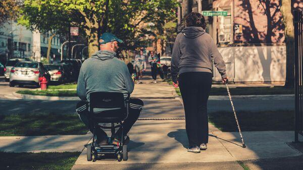 Мужчина в коляске гуляет с женщиной с тростью - Sputnik Узбекистан