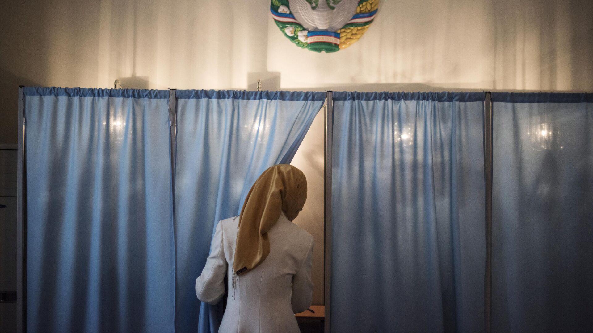 Женщина голосует на избирательном участке во время выборов президента Узбекистана. Архивное фото - Sputnik Узбекистан, 1920, 26.09.2021