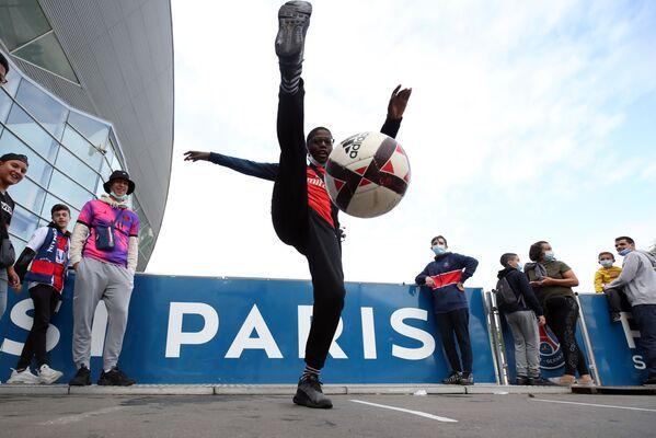 В ожидании прибытия кумира поклонники Месси играют в футбольный мяч у ворот стадиона. - Sputnik Узбекистан