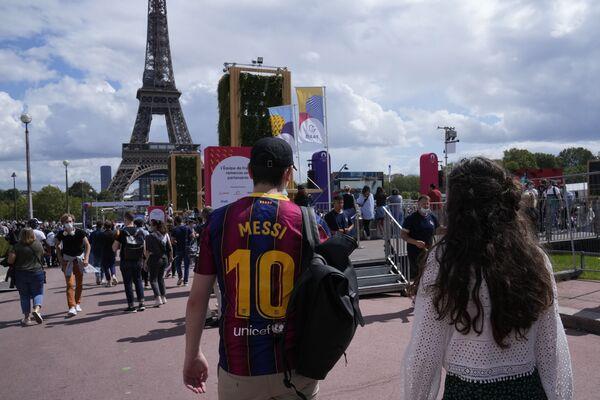 Зритель в футбольной майке Лионеля Месси гуляет по олимпийской фан-зоне в садах Трокадеро перед Эйфелевой башней в Париже. - Sputnik Узбекистан