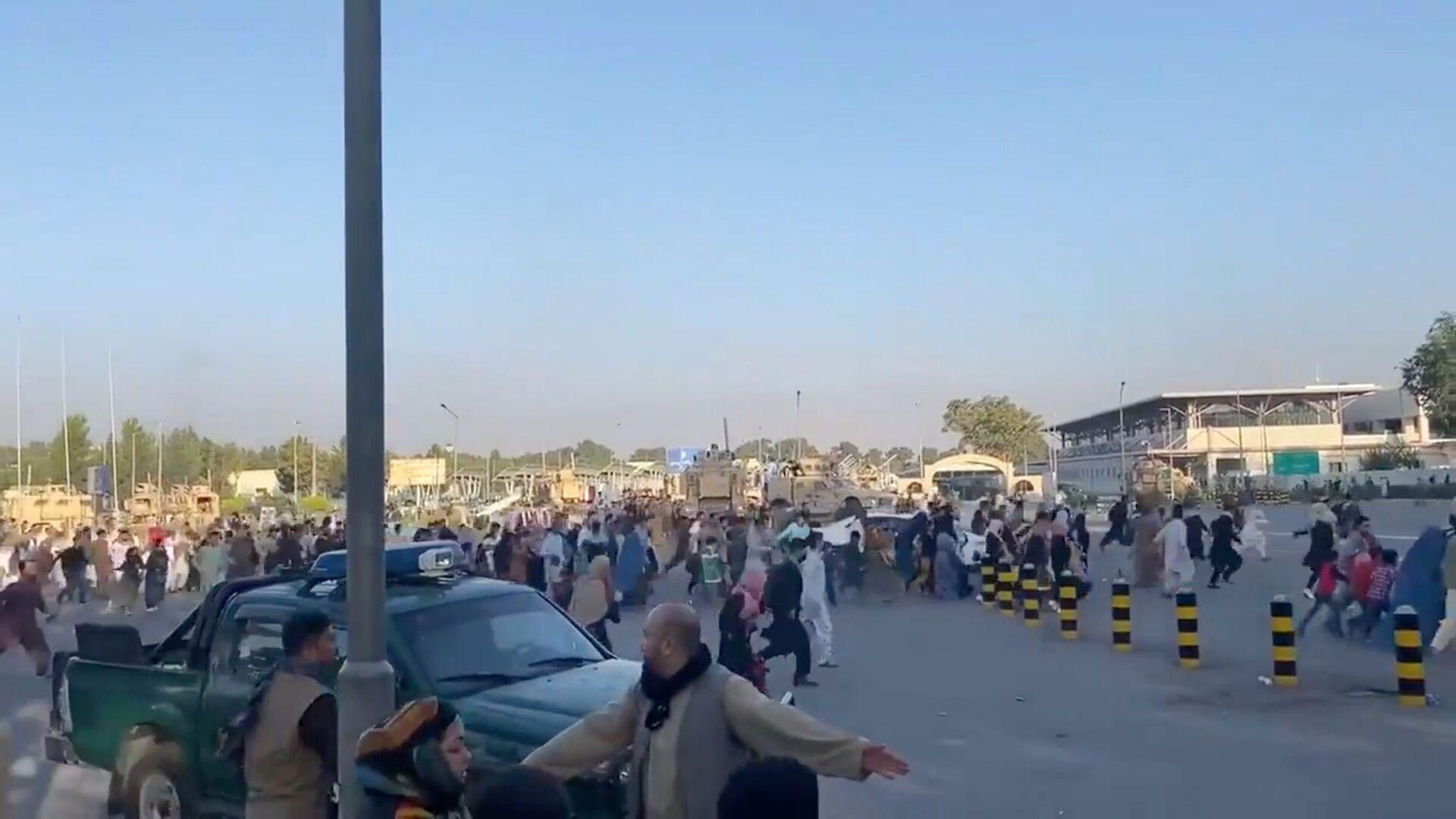 Люди бегут к терминалу Кабульского аэропорта после захвата президентского дворца группировкой Талибан* - Sputnik Узбекистан, 1920, 26.08.2021