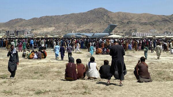 Сотни людей собрались возле транспортного самолета C-17 ВВС США на периметре международного аэропорта в Кабуле - Sputnik Узбекистан
