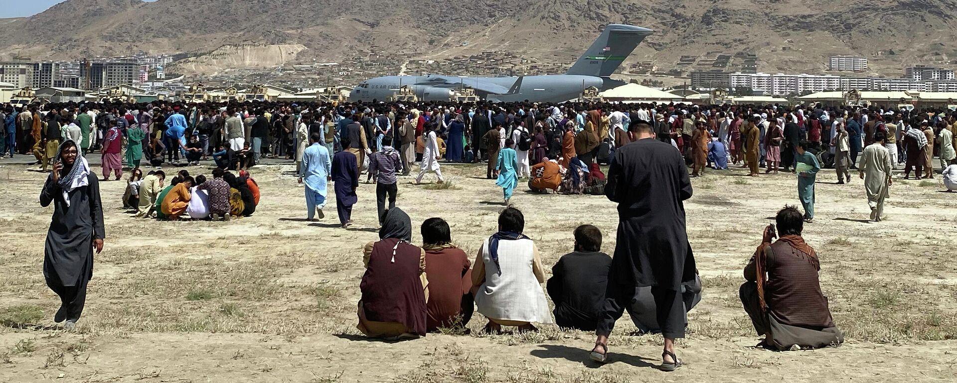 Сотни людей собрались возле транспортного самолета C-17 ВВС США на периметре международного аэропорта в Кабуле - Sputnik Узбекистан, 1920, 31.08.2021