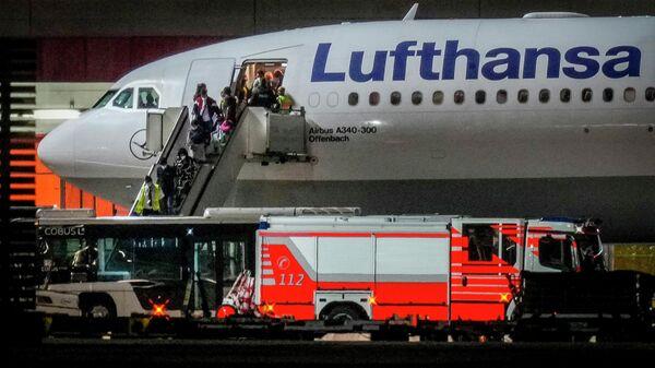 Люди высаживаются из самолета Lufthansa, прилетевшего из Ташкента в Узбекистан, который приземлился в аэропорту Франкфурта, Германия, рано утром в среду, 18 августа 2021 года. На борту находилось около 130 человек, которые ранее были эвакуированы из Афганистана - Sputnik Узбекистан