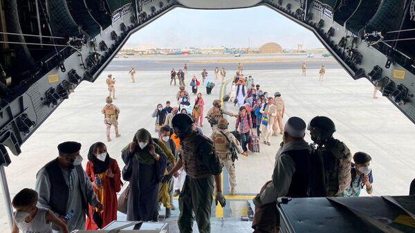 Граждане Испании и афганцы садятся в военный самолет в рамках эвакуации в международном аэропорту Хамида Карзая в Кабуле - Sputnik Узбекистан