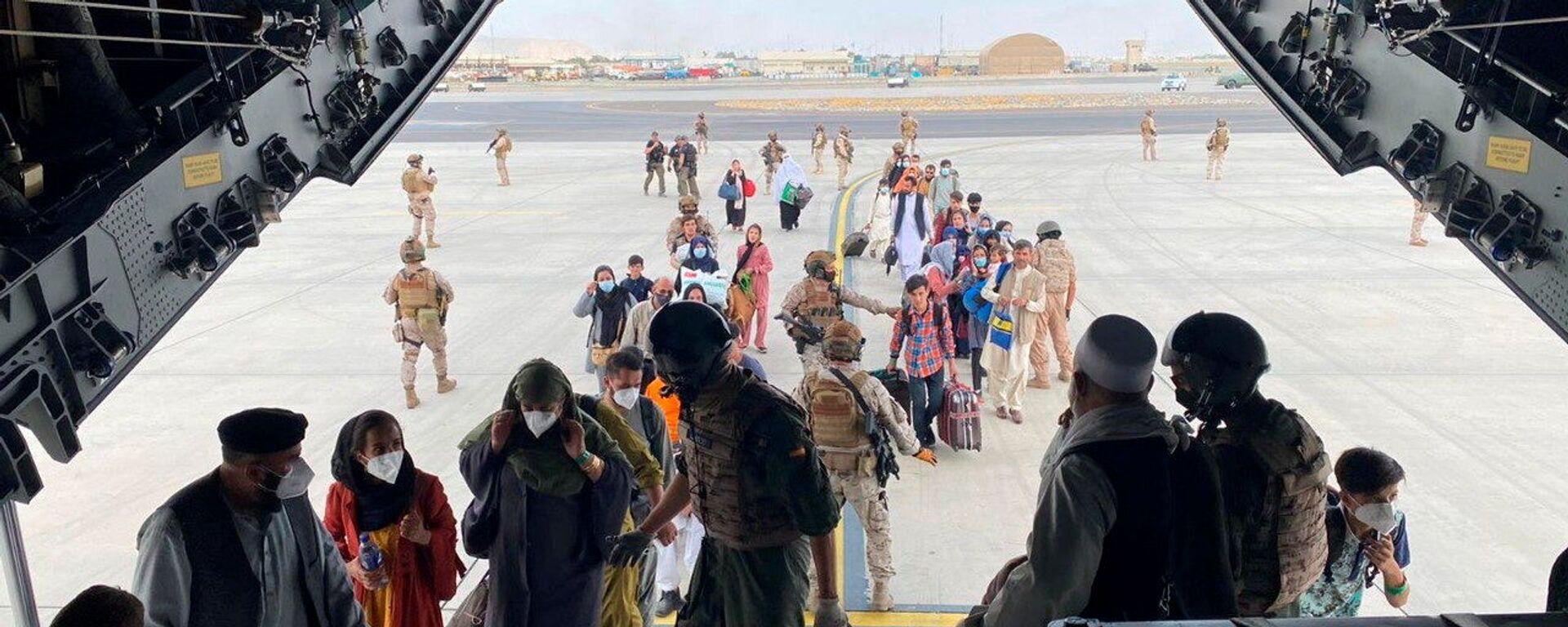 Граждане Испании и афганцы садятся в военный самолет в рамках эвакуации в международном аэропорту Хамида Карзая в Кабуле - Sputnik Узбекистан, 1920, 22.08.2021