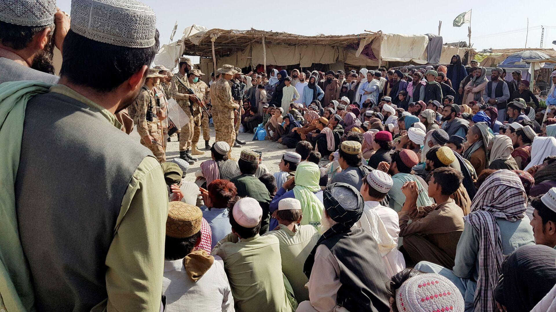 Солдаты пакистанской армии разговаривают с людьми, которые собираются пересечь пункт пропуска в пакистано-афганском пограничном городе Чаман - Sputnik Узбекистан, 1920, 23.08.2021