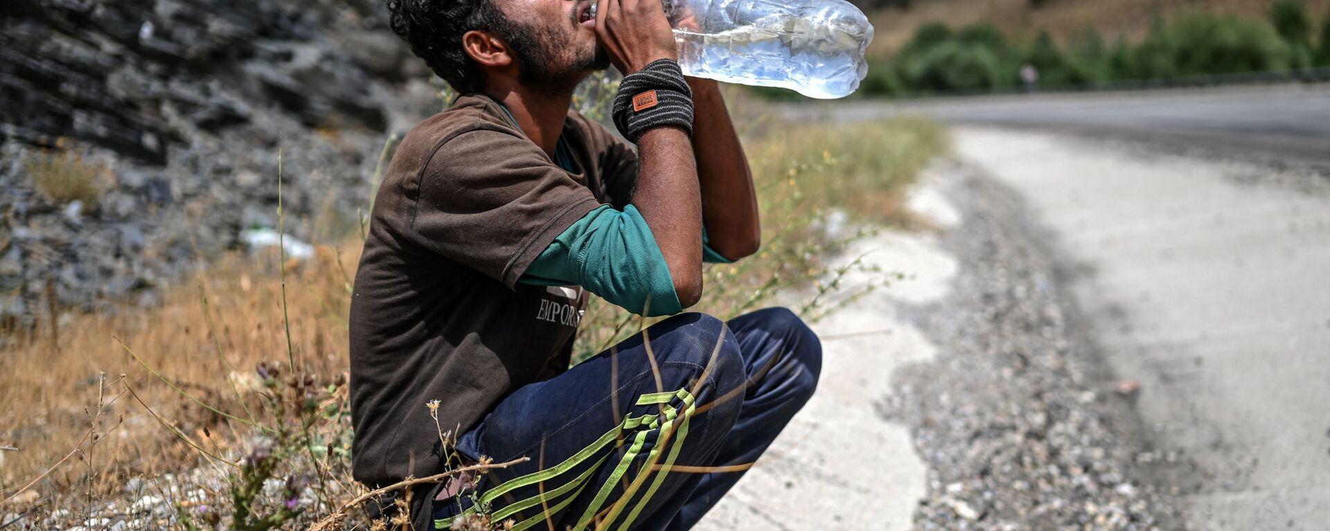 Афганский мигрант пьет воду в Татване - Sputnik Ўзбекистон, 1920, 16.09.2021