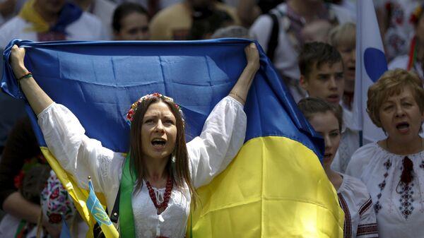 Женщина в вышиванке с украинским флагом на марше в Киеве, Украина - Sputnik Узбекистан
