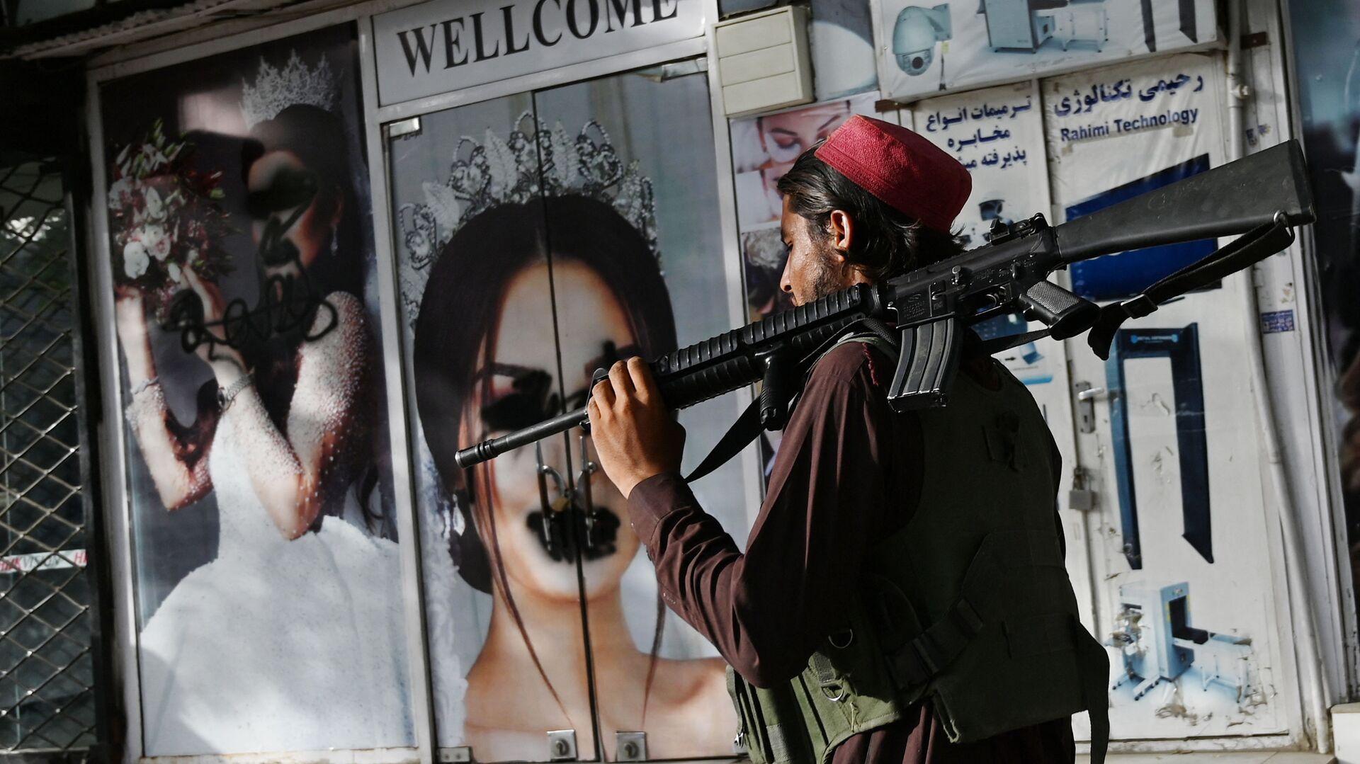 Боевик Талибана* у салона красоты с изображениями женщин, испачканных аэрозольной краской, в Шахр-э Нау в Кабуле - Sputnik Ўзбекистон, 1920, 08.10.2021