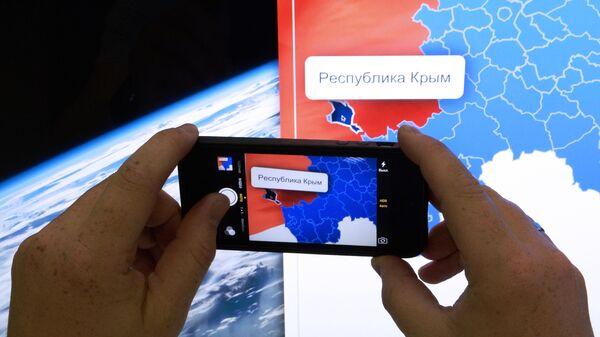 Мужчина фотографирует на телефон карту России с включенной в ее состав республикой Крым - Sputnik Узбекистан
