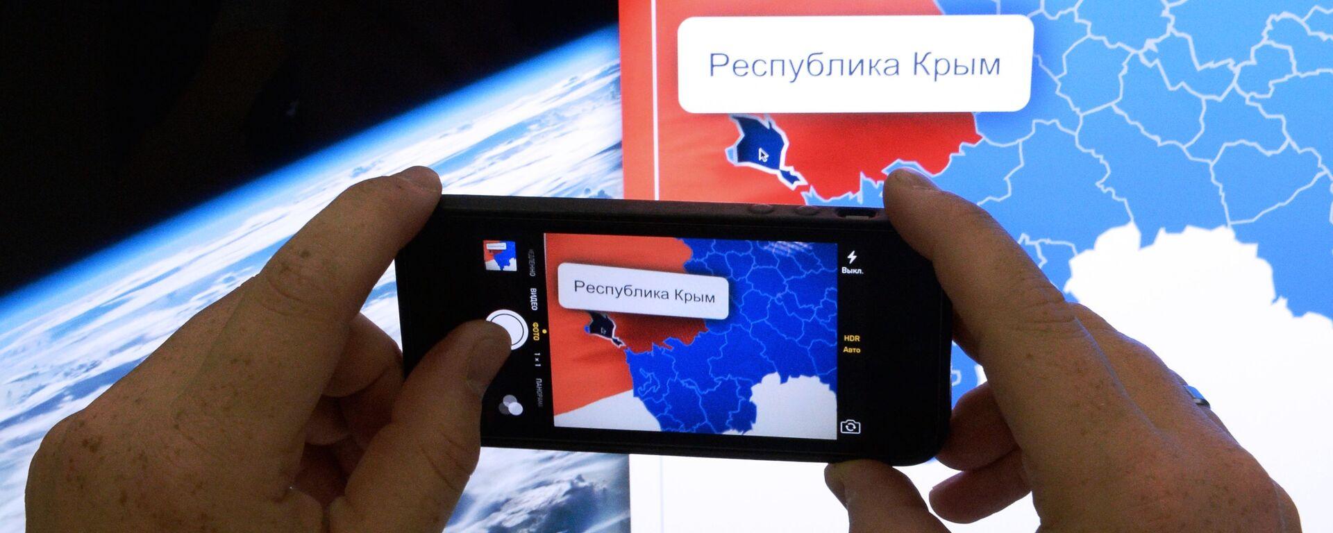 Мужчина фотографирует на телефон карту России с включенной в ее состав республикой Крым - Sputnik Узбекистан, 1920, 24.08.2021
