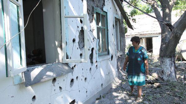 Женщина у жилого дома в поселке Новая Марьевка в Донецкой области, пострадавшего в результате ночного обстрела - Sputnik Узбекистан