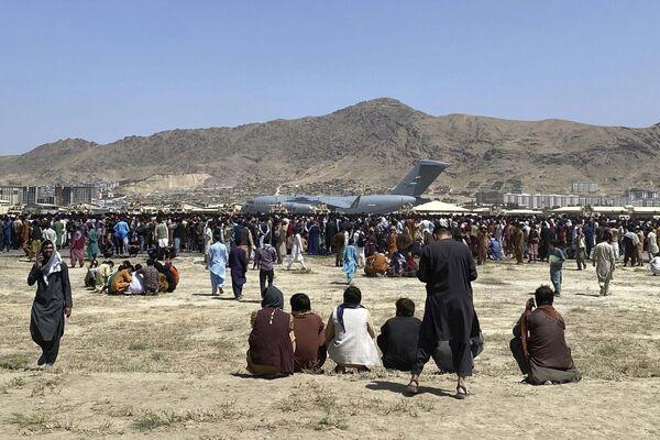Сотни людей собрались возле самолета C-17 в аэропорту Кабула в надежде покинуть свою родину. - Sputnik Узбекистан