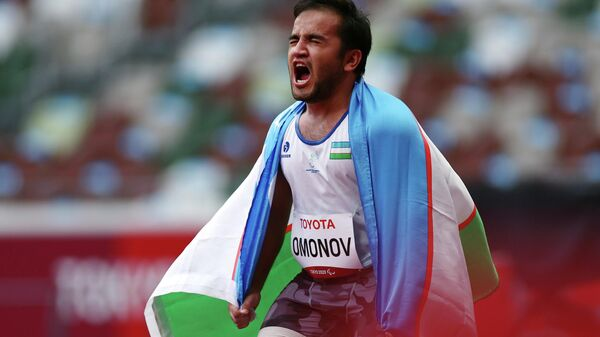 Bobirjon Omonov of Uzbekistan reacts after winning gold and setting a new Paralympic record with the flag of Uzbekistan REUTERS/Athit Perawongmetha - Sputnik Ўзбекистон