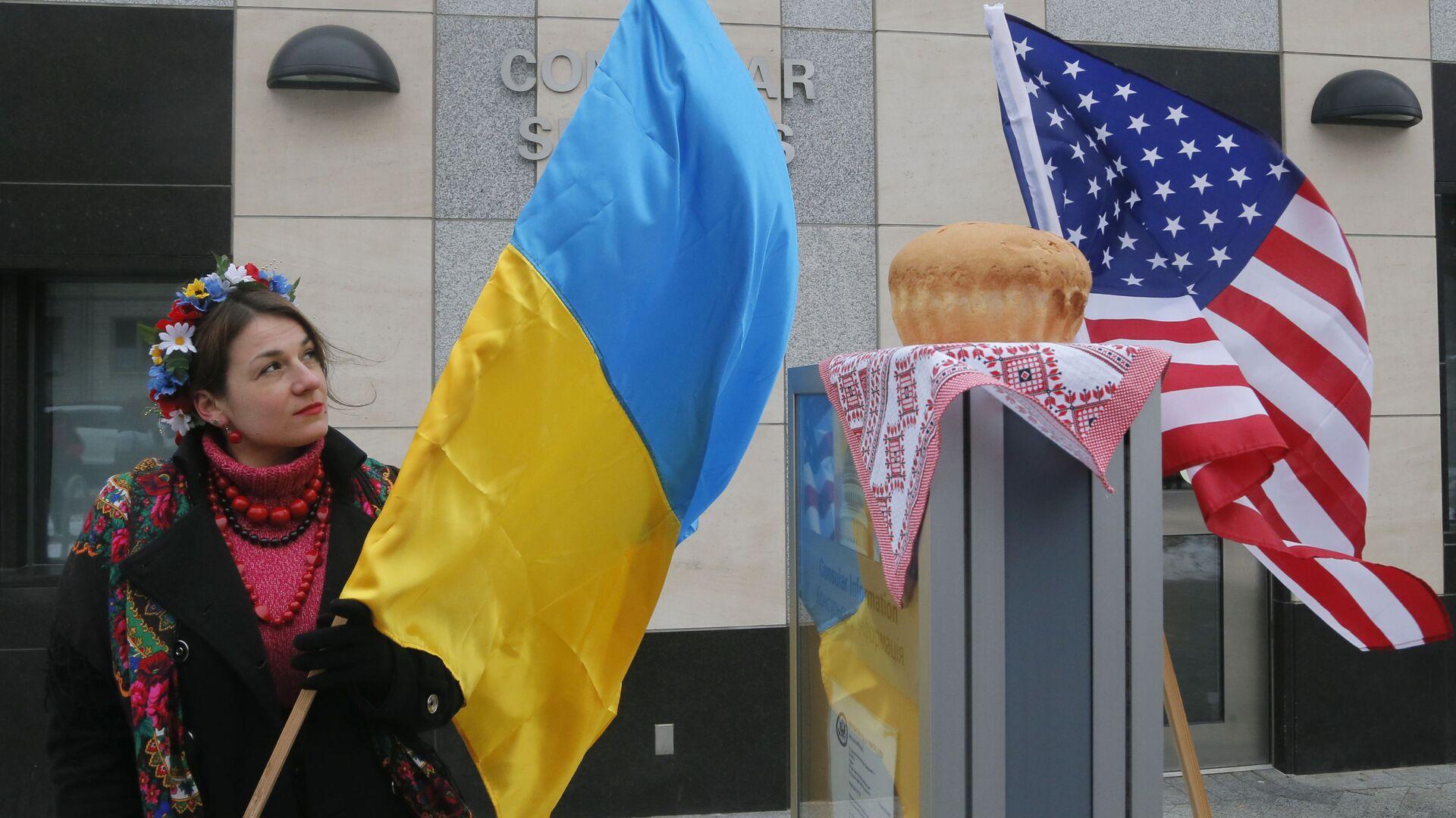 Девушка с украинским флагом у посольства США в Киеве  - Sputnik Узбекистан, 1920, 17.09.2021