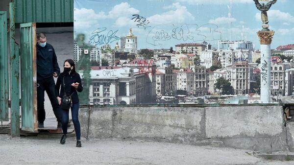 Люди в масках проходят мимо баннера с изображением Киева - Sputnik Узбекистан