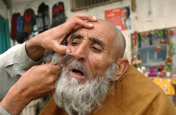 Уличный парикмахер бреет клиента в Джелалабаде, 2006 год. - Sputnik Узбекистан
