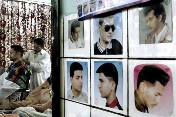 В парикмахерской на стене висят фотографии, на которых изображены разные стили стрижки без бороды, Кабул, 2002 год. - Sputnik Узбекистан