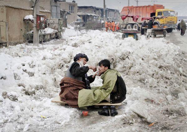 Уличный парикмахер бреет клиента во время снегопада в Кабуле, 2012 год. - Sputnik Узбекистан