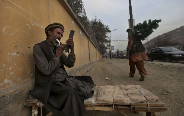 Придорожный парикмахер стрижет себе бороду, ожидая клиентов, Кабул, 2010 год. - Sputnik Узбекистан