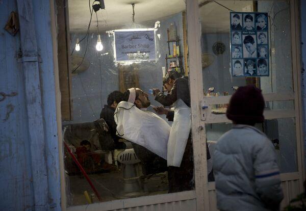 Мальчик заглядывает в парикмахерскую, где мужчине подстригают бороду, Кабул, 2013 год. - Sputnik Узбекистан