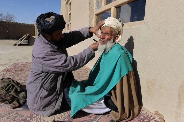 Деревенский цирюльник стрижет мужчине бороду в афганской провинции Газни, 2011 год. - Sputnik Узбекистан