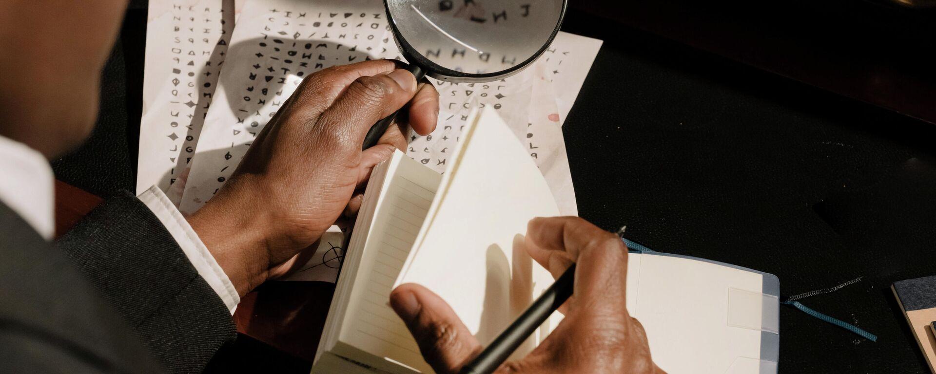 Мужчина рассматривает текст под увеличительным стеклом - Sputnik Узбекистан, 1920, 06.10.2021