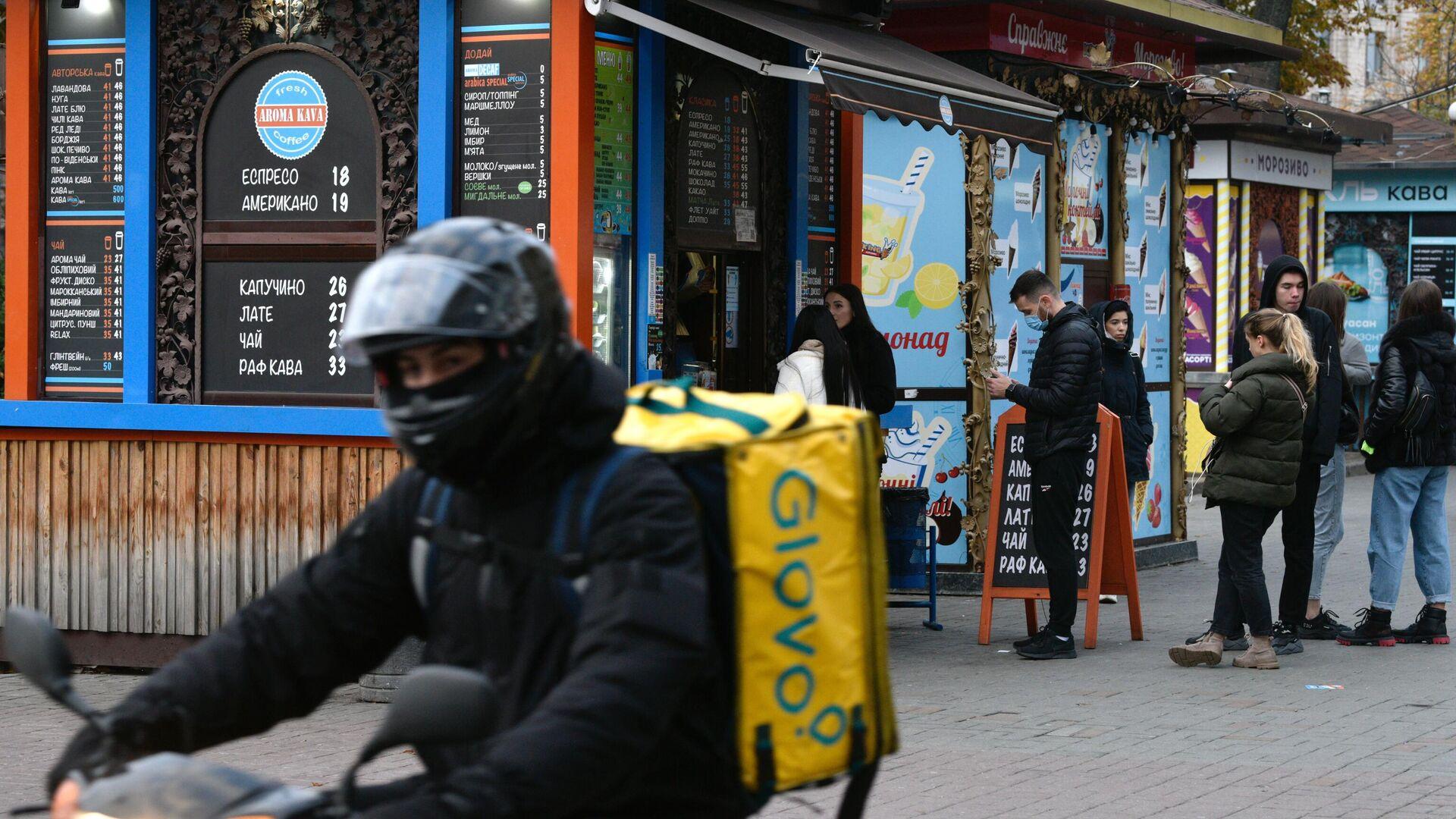 Курьер службы доставки на одной из улиц в Киеве. - Sputnik Узбекистан, 1920, 08.10.2021