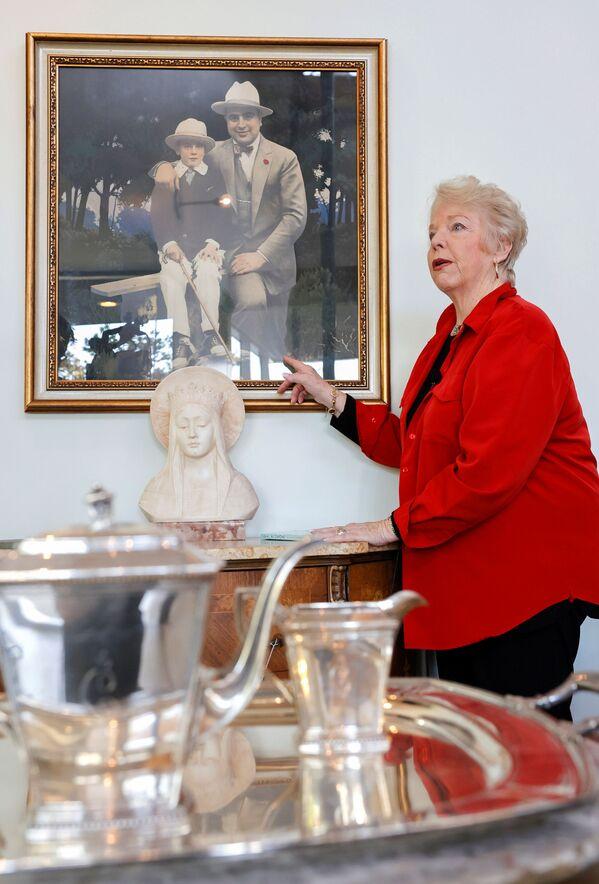 Дайан Капоне, внучка гангстера Аль Капоне, стоит рядом с картиной, изображающей ее деда и отца Сонни Капоне. Фото сделано 5 октября 2021 года. - Sputnik Узбекистан