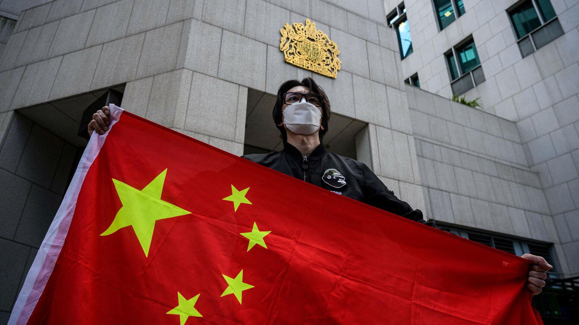 Мужчина держит флаг Китая - Sputnik Узбекистан, 1920, 09.10.2021