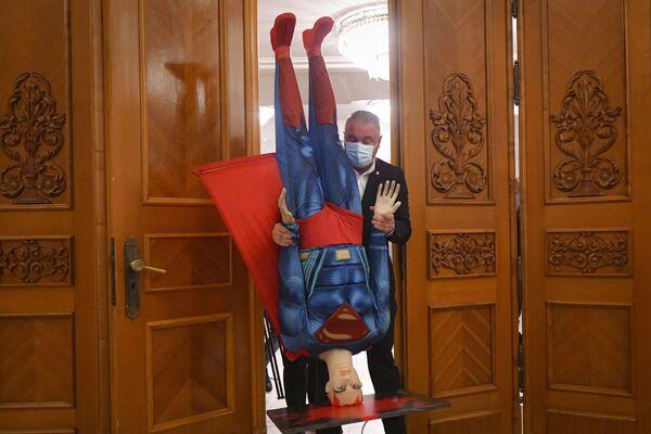 Руминия парламенти аъзоси Супермен манекенни тескари ушлаб турибди. - Sputnik Ўзбекистон