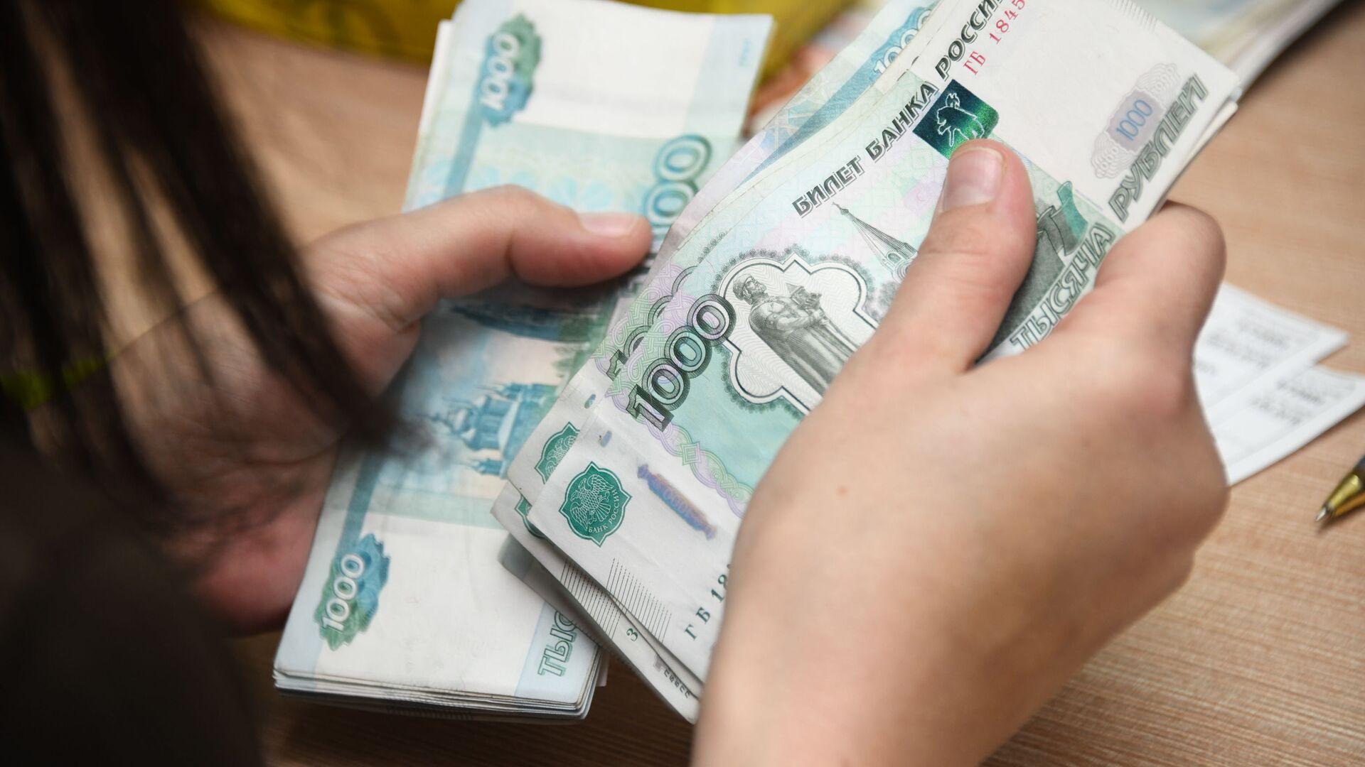 Работник почтамта пересчитывает деньги - Sputnik Узбекистан, 1920, 12.10.2021