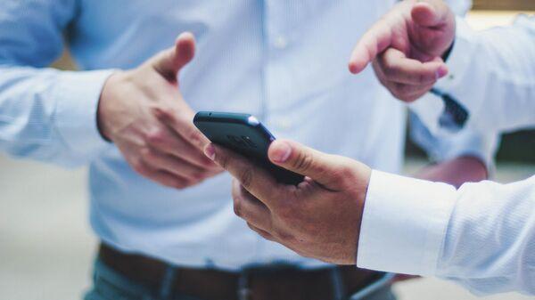 Мобильный телефон в руке мужчины - Sputnik Узбекистан
