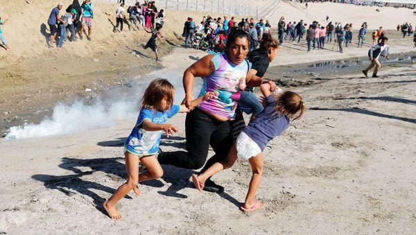 Мигранты из Гондураса бегут от слезоточивого газа, распыленного американскими пограничниками - Sputnik Ўзбекистон