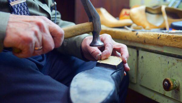 Сапожник ремонтирует обувь, архивное фото - Sputnik Узбекистан