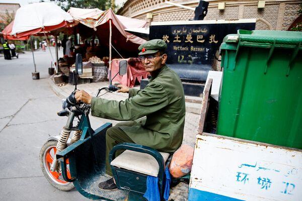 Мужчина вывозит мусор на мопеде в Кашгаре, Синьцзян-Уйгурский автономный район, Китай - Sputnik Узбекистан
