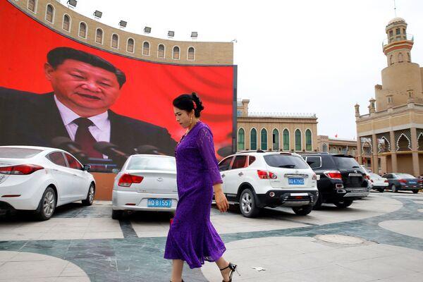 Женщина у гигантского экрана на главной городской площади в Кашгаре, Синьцзян-Уйгурский автономный район, Китай - Sputnik Узбекистан