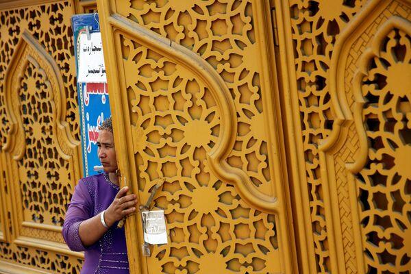Женщина у двери в Старом городе в Кашгаре, Синьцзян-Уйгурский автономный район, Китай - Sputnik Узбекистан