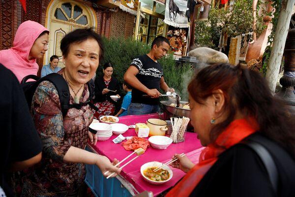 Туристы обедают в Старом городе в Кашгаре, Синьцзян-Уйгурский автономный район, Китай - Sputnik Узбекистан