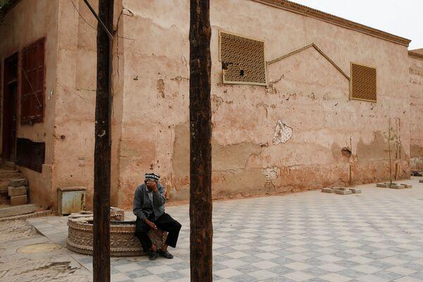 Пожилой мужчина закрывает лицо от камеры в Кашгаре, Синьцзян-Уйгурский автономный район, Китай - Sputnik Узбекистан