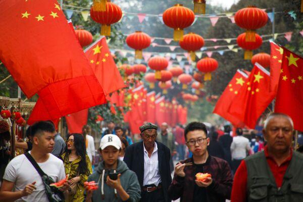 Люди проходят мимо китайских флагов в Кашгаре, Синьцзян-Уйгурский автономный район, Китай - Sputnik Узбекистан