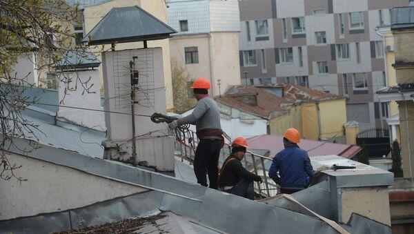 Рабочие-строители на крыше здания в Москве. - Sputnik Узбекистан