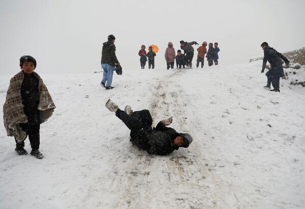 Дети катаются с горки во время снегопада в Кабуле - Sputnik Узбекистан